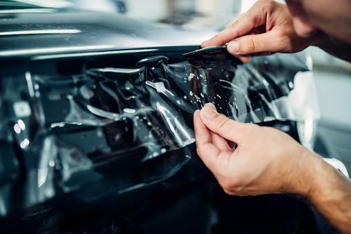 Specialist installs car paint protection film on hood. Transparent protective coating against chips and scratches